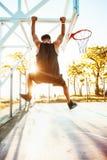 De basketbalspeler hangt op de rand sportuitrusting, sportcompetities Stock Afbeelding