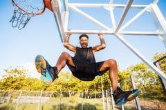 De basketbalspeler hangt op de rand sportuitrusting, sportcompetities, straatbal, sportman Royalty-vrije Stock Afbeeldingen