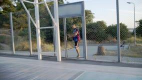 De basketbalspeler komt aan de speelplaats voor het spel De basketbalspeler speelt bij de dageraad van de zon stock videobeelden