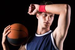 De basketbalspeler veegt het zweet van zijn voorhoofd af stock afbeelding
