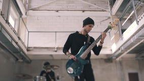 De bassist en de slagwerker spelen de laatste zinsnede van de samenstelling De basgitarist en beëindigt effectief artistiek zijn  stock footage