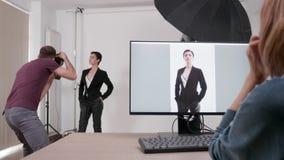 De bastidores de um profissional que photoshooting onde o cliente est? olhando vivo nas imagens video estoque