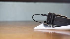 De batterij chager legt op wit blad, op houten lijst Stock Foto's