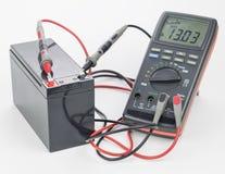 De batterij wordt aangesloten aan een digitale meter op een witte achtergrond stock foto