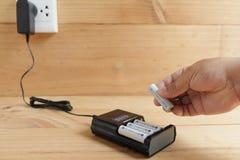 De batterijgrootte aa van de handholding navulbaar met Lader stock foto
