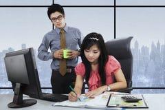 De bazige manager kijkt zijn arbeider het werken Stock Afbeeldingen