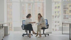 De beambten die twee jonge vrouwen zitten die op bureau zitten zit het onderhandelen documenten van de firma voor, verklaart één  stock video