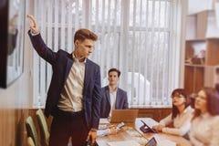 De beambten houden een vergadering bij ??n bureau voor laptops, tabletten en documenten, op de achtergrond een grote Televisie op stock fotografie