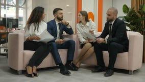 De beambten twee jonge mannen en twee jonge vrouwen die op de banken zitten bespreken belangrijke documenten van de firma, stock footage