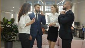 De beambten zich twee jonge mannen en twee jonge vrouwen bevinden en bespreken een belangrijk project van de firma, emotioneel stock footage
