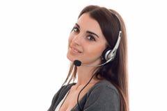 De beambtevrouw van de Cutie jonge donkerbruine vraag met hoofdtelefoons en microfoon glimlachen geïsoleerd op witte achtergrond Royalty-vrije Stock Afbeeldingen