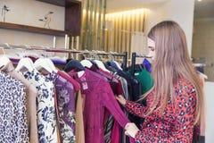 De beaux achats de femme dans un magasin de mode photographie stock libre de droits