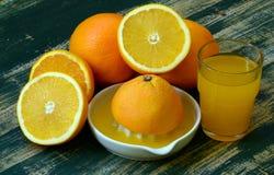 De beaux-arts toujours la vie avec le jus d'orange et le presse-fruits de porcelaine sur la table en bois photos stock