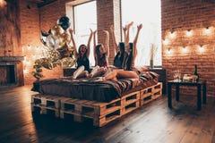 De beaux quatre amis joyeux de taille du corps de rire intégral de photo elle ses bras de mains augmentés vers le haut des dames  photo libre de droits