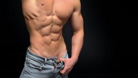 De bebouwde foto van een sportieve mens met een spierlichaam knoopt overhemd en jeans los die in studio binnen stellen royalty-vrije stock foto