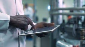 De bebouwde wetenschapper overhandigt klikkende tablet in laboratorium stock videobeelden