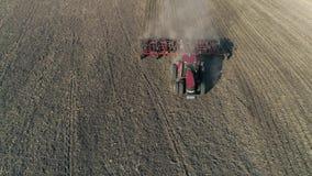De bebouwing, landbouwbedrijftractor met ploeg cultiveert grond op gebied alvorens landbouwgewassen te zaaien stock video