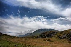 De bedöva welsh bergen under en molnig blå himmel Arkivfoto