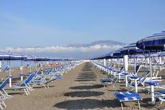 De bedden en de paraplu's van de plank op een strand Stock Foto's