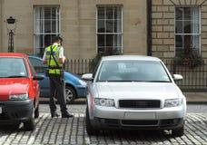 De bediende van het parkeren, verkeershoofd, dat kaartjes fijn mandaat krijgt Royalty-vrije Stock Foto