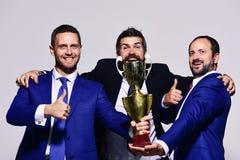 De bedrijfleiders houden gouden prijs, tonen duimen en omhelzing stock foto