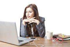 De bedrijfs aantrekkelijke vrouw geniet van met het luisteren muziek op het bureau Stock Fotografie