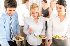 De bedrijfs collega's dienen zich bij buffet stock foto