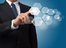 De bedrijfs mens duwt een hexagonale knoop van het aanrakingsscherm Stock Foto's