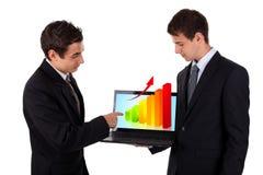 De bedrijfs mens toont op laptop met grafiek 2 Stock Afbeeldingen