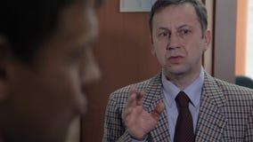 De bedrijfs volwassen werkgever berispt de arbeidersmens in bureaukabinet stock video