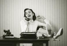 Vrouw die op telefoon bij bureau spreken stock fotografie