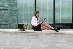 De bedrijfs vrouwenzitting en ondertekent het document Royalty-vrije Stock Afbeeldingen