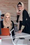 De bedrijfscollega's die in hijabs de computer bekijken controleren stock afbeeldingen