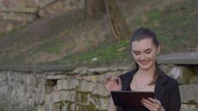 De bedrijfsdame geniet van tablet in park en het smilling langzaam stock footage