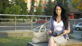 De bedrijfsdamezitting op een bank trekt haar notitieboekje uit de zak om een herinnering te schrijven De jonge vrouw schrijft ee stock video