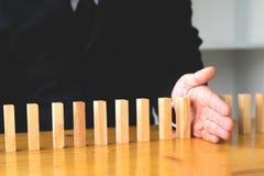 De bedrijfshand houdt domino ononderbroken ten val gebrachte betekenis tegen die hallo royalty-vrije stock afbeeldingen