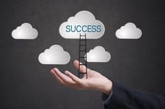 De bedrijfshand met ladder verovert succes op wolk royalty-vrije stock afbeeldingen