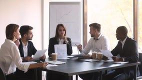 De bedrijfsleider onderhandelt met diverse cliënten zit bij conferentielijst stock footage