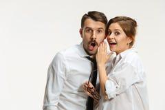 De bedrijfsman en de vrouw die op een grijze achtergrond communiceren stock fotografie
