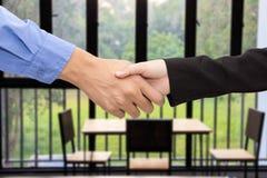 De bedrijfsman en vrouwenhanddruk blured vergaderzaalbackgrou Stock Foto