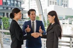 De bedrijfsman toont duim en twee het bedrijfsvrouw schudden handen voor het aantonen van hun overeenkomst aan tekenovereenkomst  Royalty-vrije Stock Fotografie
