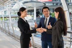 De bedrijfsman toont duim en twee het bedrijfsvrouw schudden handen voor het aantonen van hun overeenkomst aan tekenovereenkomst  Stock Afbeeldingen