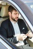 De bedrijfsmens in de auto leest bericht op tablet royalty-vrije stock fotografie