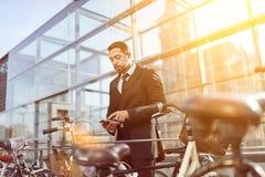 De bedrijfsmens beveiligt fiets met slim slot stock fotografie