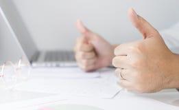 De bedrijfsmens in bureau is optimistisch met omhoog duimen Stock Foto's