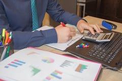 De bedrijfsmens die financiën doet berekent analyse werkend met de financiële grafiek van de de verkoopvoorspelling van de result stock foto's