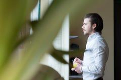 De bedrijfsmens drinkt een koffie, bureau Stock Foto