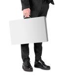 De bedrijfsmens in een zwart kostuum en schoenen houdt een witte doos met een handvat Stock Afbeeldingen
