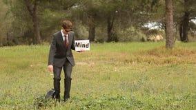 De bedrijfsmens en twee jongeren met zelf gemaakt uithangbord met het woord brengen mindfulness in verwarring stock video