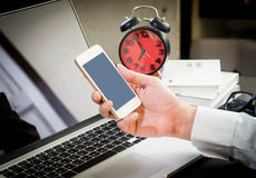 De bedrijfsmens gebruikt zijn smartphone op bureau stock afbeeldingen
